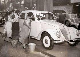 Putzfrauen begutachten eine Luxus-Limousine bei der Automobilausstellung in London 1936. Photographie