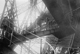 Menschen besteigen den Eiffelturm, während ein Mann mit seinem Fahrrad die Treppe hinunterfährt. Paris. Photographie