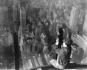 Bauarbeiter, der auf einem Gerüst sitzt, blickt über New York. Photographie