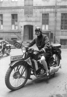 Eine Motorradfahrerin auf ihrer Maschine. Photographie