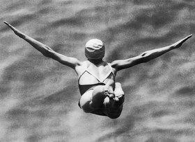 Eine Turmspringerin beim Sprung ins Wasser. Photographie