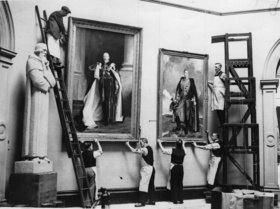Portraitgemälde von George V. und George VI.werden in der Burlington Galerie aufgehängt. London. England. Photographie