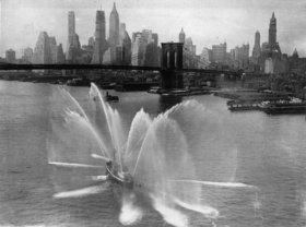 Das Feuerwehrschiff von New York bei der täglichen Übung. Im Hintergrund Brooklyn Bridge und die Skyline von New York. Amerika. Photographie