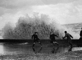Nach dem Hochwasser in Hastings fliehen einige Buben vor den Wellen. Photographie. England