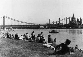Badende an der Wiener Donau, im Hintergrund die Reichsbrücke. Wien. Österreich. Photographie