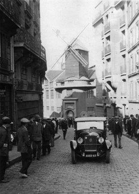 Autorennen im Montmartre in Paris. Im Hintergrund: das Moulin Rouge. Photographie