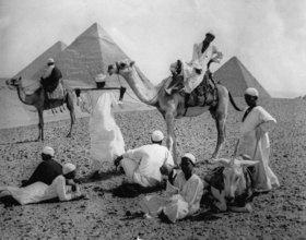 Kamele und ihre Reiter während einer Rast vor Pyramiden in Ägypten. Photographie