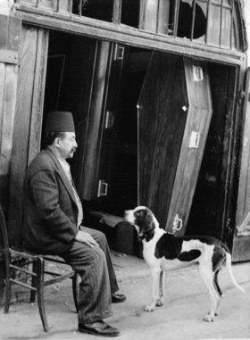 Sargverkäufer mit seinem Hund vor einer Reihe von Särgen in Jerusalem. Photographie