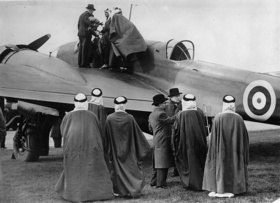 Besichtigung von Englands neuestem Flugzeugen. Oben auf der Tragfläche der Anführer der arabischen Delegation Prinz Feisal. Photographie