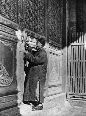 Der Hüter des Konfuziustempels in Nordchina öffnet das chinesische Schloss, um die großen Torflügel zu öffnen. Photographie