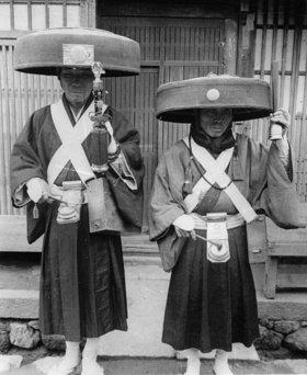 Zwei japanische Priester vor einem Tempel, die Gläubige mit Hilfe von speziellen Klängen zum Gebet rufen. Sie tragen dabei ihre traditionelle Kopfbedeckung. Photographie