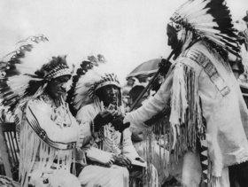 Indianer beim Rauchen einer Friedenspfeife. Photographie