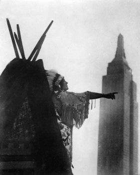 Indianer zeigt von seinem Zelt aus auf einen Wolkenkratzer. Photographie