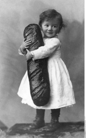 Ein kleines Kind hält einen grossen Laib Brot im Ar