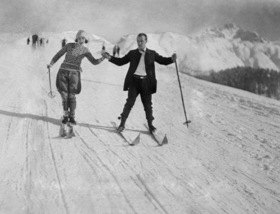 Ein Pärchen auf Skiern fährt einen Berg herunter. Um 1920.