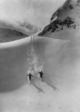 Zwei Skifahrer bei der Abfahrt im verschneiten Hochgebirge