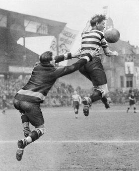 Martin Munkásci: Tormann und Fussballspieler springen nach einem Ball